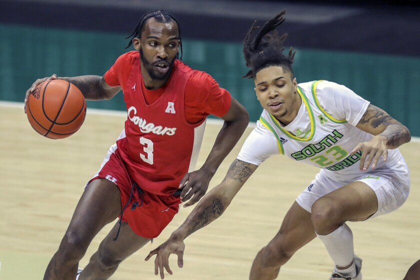 Houston's DeJon Jarreau, left, drives past South Florida's Caleb Murphy during the first half of an NCAA college basketball game Wednesday, Feb. 10, 2021, in Tampa, Fla. (AP Photo/Mike Carlson)