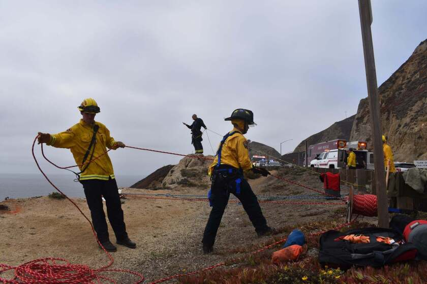 In this photo provided by CAL FIRE San Mateo Santa Cruz Unit firefighters recover a vehicle that plunged off a cliffside road killing a man south of San Francisco and landed on a beach more than 200 feet (60 meters) below on Wednesday, Sept. 15, 2021. Authorities, responding to a 911 call that a vehicle had gone over the cliff, found the car then used a drone to locate the driver, who had been ejected from the vehicle, said Mark Andrews, a spokesman for the California Highway Patrol. (CAL FIRE San Mateo- Santa Cruz Unit via AP)