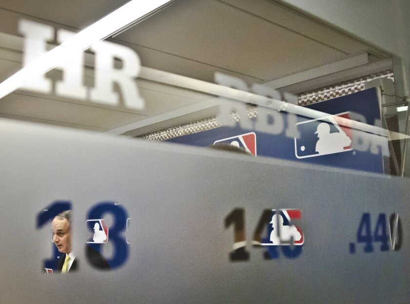 Baseball commissioner Rob Manfred is viewed through a glass wall panel, engraved with baseball statistics, during a press conference after his first owners' meeting as baseball commissioner, Thursday, May 21, 2015, in New York. (AP Photo/Bebeto Matthews)