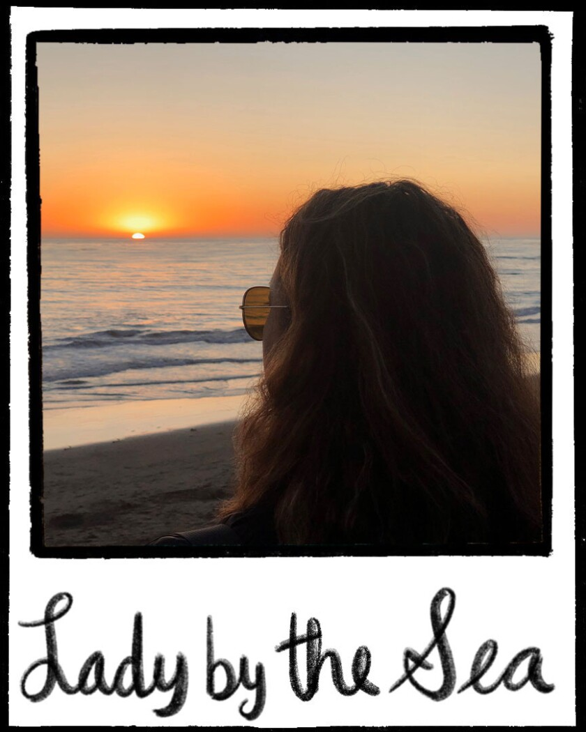 Illustrated polaroid frame with a photo of a woman looking at a beach sunset. 'Lady by the Sea' is written at bottom of frame