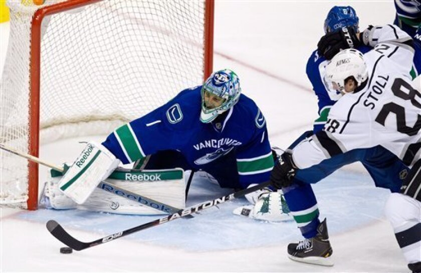 Vancouver Canucks' goalie Roberto Luongo, left, stops Los Angeles Kings' Jarret Stoll during the second period of an NHL hockey game in Vancouver, British Columbia on Monday March 26, 2012. (AP Photo/The Canadian Press, Darryl Dyck)
