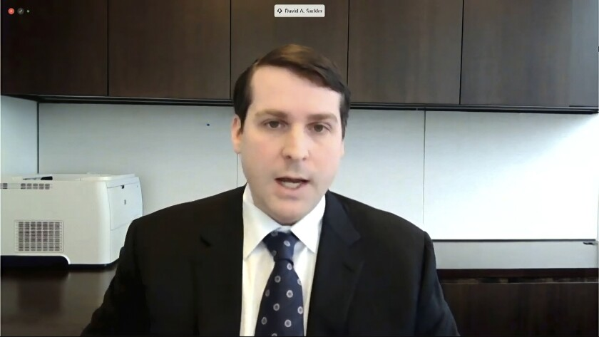 David Sackler appears in a video stream from an office