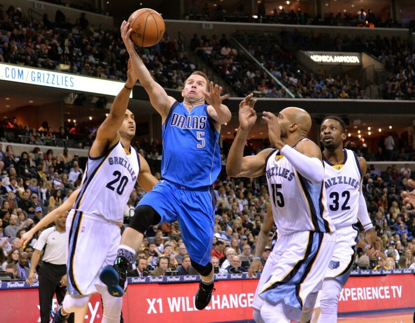 Dallas Mavericks guard J.J. Barea (5) shoots between Memphis Grizzlies center Ryan Hollins (20), guard Vince Carter (15), and forward Jeff Green (32)  in the first half of an NBA basketball game Saturday, Feb. 6, 2016, in Memphis, Tenn. (AP Photo/Brandon Dill)
