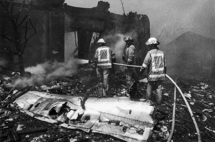 Aug. 31, 1986: Firefighters mop up embers from burned-out home and aircraft pieces.