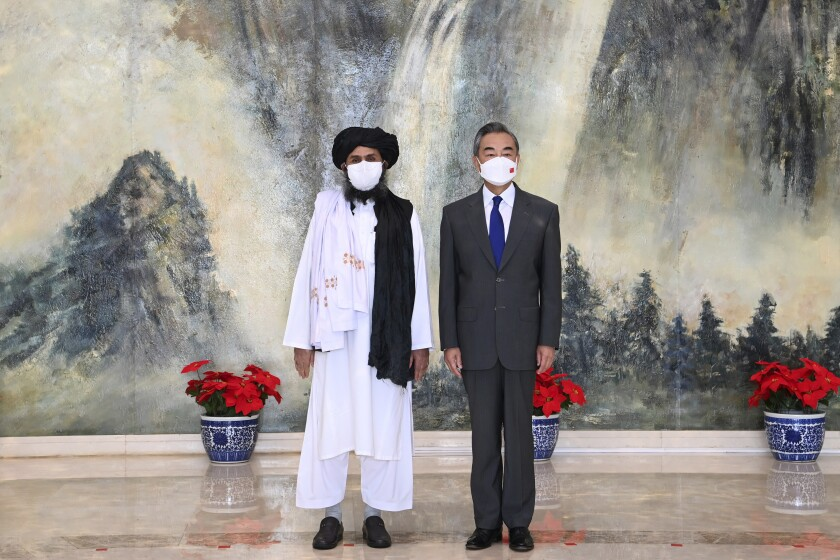 Taliban co-founder Mullah Abdul Ghani Baradar, left, and Chinese Foreign Minister Wang Yi meet in Tianjin, China.