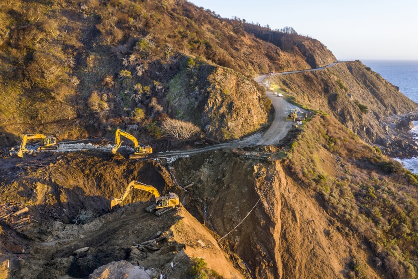 Crews dig out debris with machinery from a washed out section of Highway 1.