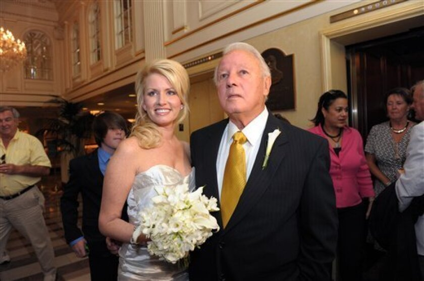 Trina Grimes Scott and former Governor Edwin Edwards greet the media after getting married in the French Quarter in New Orleans, La., Friday, July 29, 2011. The four-time ex-governor, who will be 84 next month, married 32-year-old Trina Grimes Scott in a simple private ceremony.  (AP Photo/Cheryl G