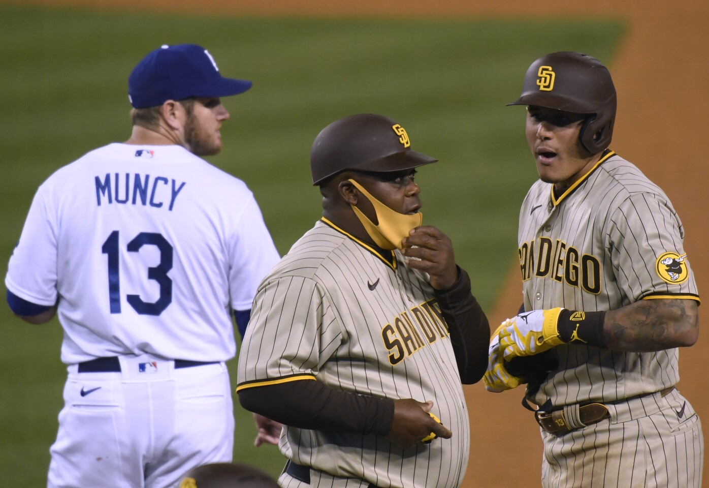 LOS ANGELES, CALIFORNIA - APRIL 22: Manny Machado #13 of the San Diego Padres reacts to his RBI single with Wayne Kirby #41 and Max Muncy #13 of the Los Angeles Dodgers, to score Fernando Tatis Jr. #23 and take a 1-0 lead, during the fourth inning at Dodger Stadium on April 22, 2021 in Los Angeles, California. (Photo by Harry How/Getty Images)