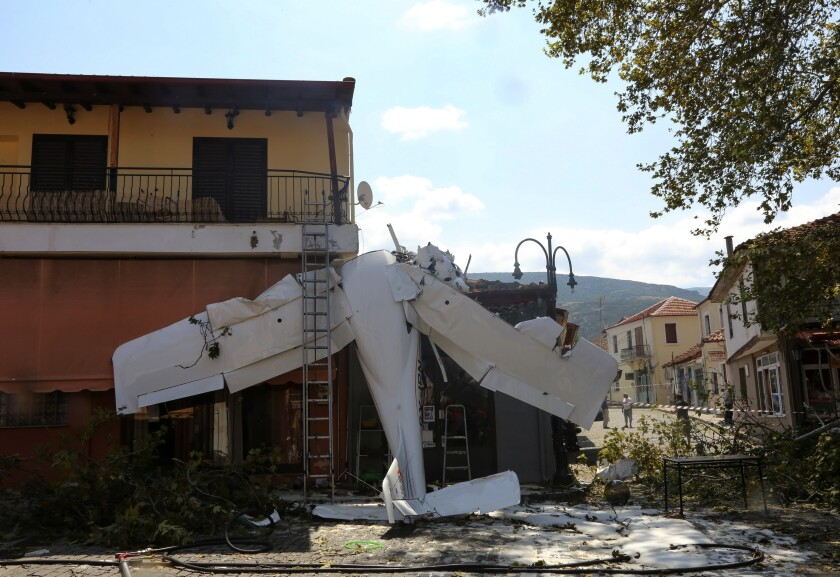 A small plane lays on a building after a crash in the village of Proti, near Serres town, northern Greece, on Monday, Aug. 3, 2020. The single-engine plane crashed on Monday morning into the front of a small building but no injuries were reported and the pilot of the Cessna aircraft is well. (Ilias Kotsireas/InTime News via AP)