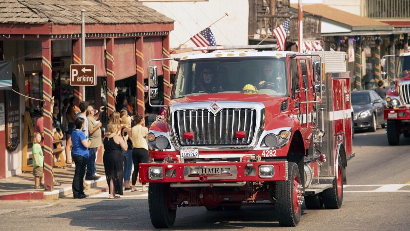 A fire truck, part of a procession carrying the body of firefighter Braden Varney, makes its way alo
