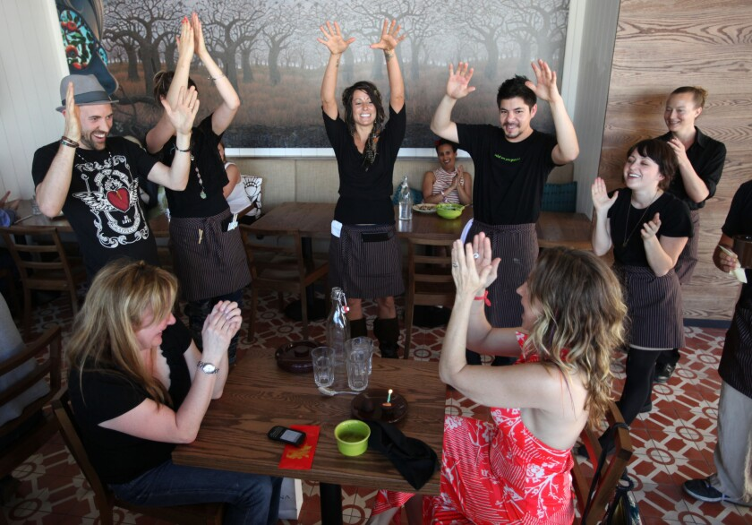 Patrons celebrate a birthday with the staff of the vegetarian restaurant Cafe Gratitude.