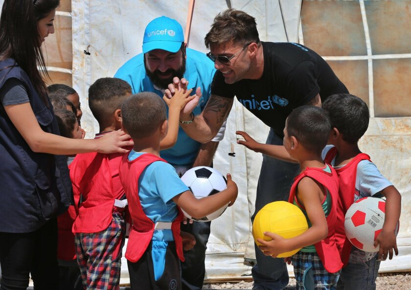 """In this picture taken on Thursday June 2, 2016, Ricky Martin, right, the world-renowned singer and UNICEF goodwill ambassador, cheers with Syrian children during his visit to an informal Syrian refugee camp, in Minnieh, near the northern city of Tripoli, Lebanon. He said that the word """"refugee"""" ha"""
