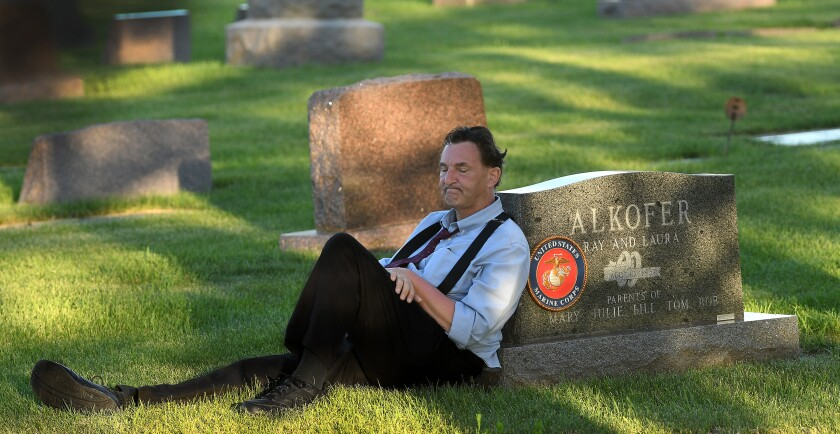 Bill Alkofer leans against his father's tombstone during a visit on the Fourth of July 2020.