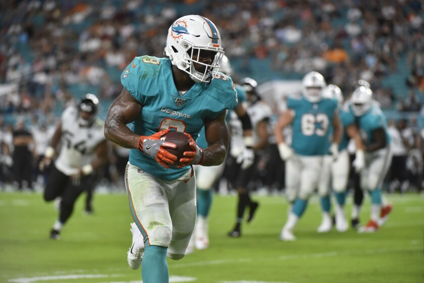 Mark Walton scores a touchdown during a preseason game against the Jacksonville Jaguars on Aug. 22. He was released Tuesday by the Miami Dolphins.