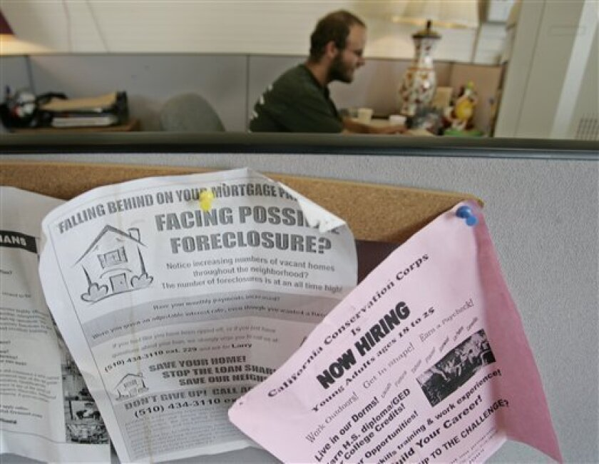 In this May 7, 2009 photo, hiring and foreclosure signs are posted at a career center in Oakland, Calif. The number of U.S. households faced with losing their homes to foreclosure jumped 32 percent in April compared with the same month last year, with Nevada, Florida and California showing the high