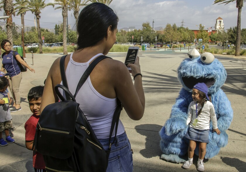Stephanie Bahena takes a photo of her daughter with Adam Sandler dressed as Cookie Monster outside the Los Angeles Zoo.
