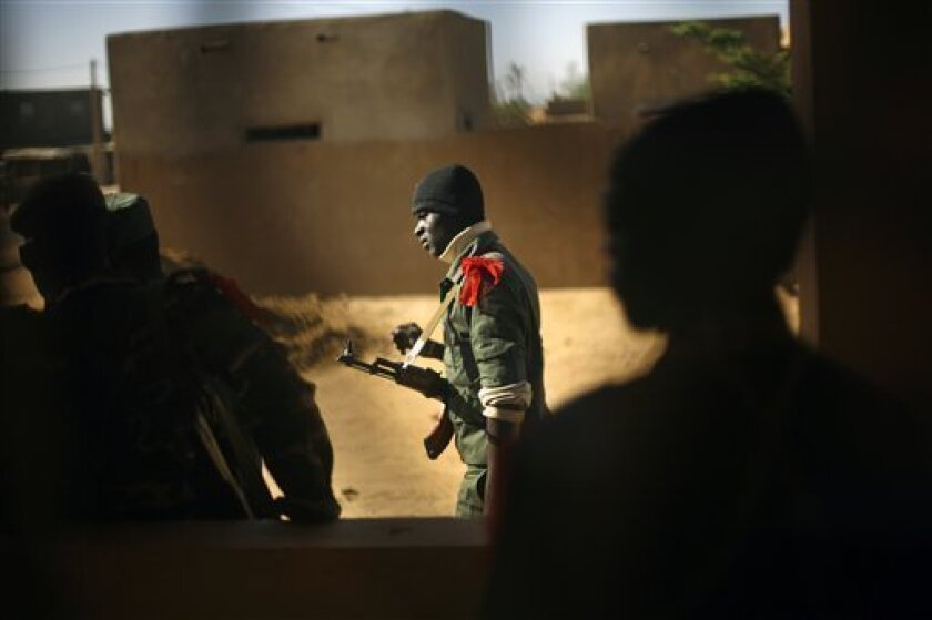 FILE In this Feb. 7, 2013 file photo, a Malian soldier walks in Gao, northern Mali. Timbuktu has been hit by a prolonged battle between Islamic extremists and the Malian and French armies, residents and a Malian military spokesman said Sunday, March 31. The attack started Saturday night at about 10