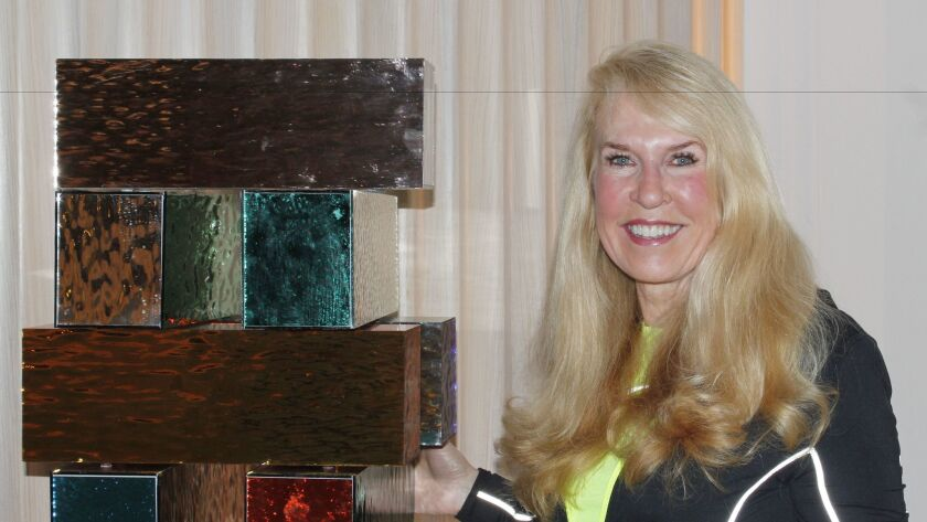 Artist and sculptor Jean Wells with one of her 5-foot Jenga-like sculptures.