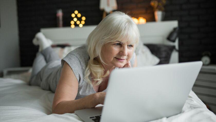 Glad senior lady lying on bed using laptop