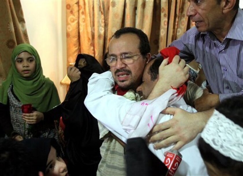 Dr. Ali al-Ekri, center, and an unidentified man hug each other at al-Ekri's home Wednesday, Sept. 7, 2011, in Daih, Bahrain, on the outskirts of the capital of Manama. Al-Ekri was one of several medical workers released from jail Wednesday pending a verdict in his trial on charges stemming from the spring uprising in the Gulf island monarchy. (AP Photo/Hasan Jamali)