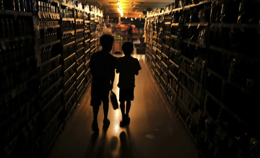 Elijah Carter and Robert Haralson shop in an Olivers Supermarket on Oct. 23, 2019, in a blackout in Santa Rosa, Calif.