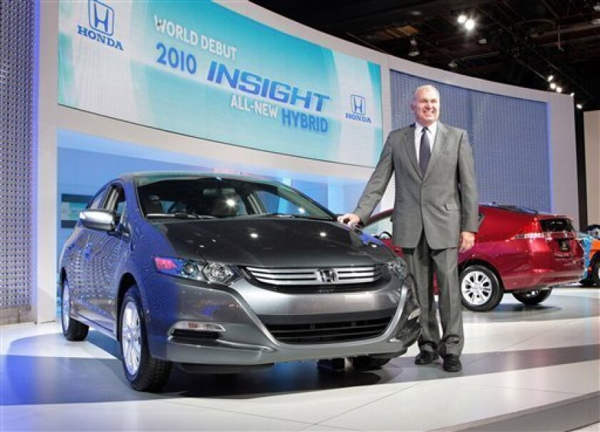 In this photo provided by Honda, John Mendel, executive vice president of American Honda Motor Co., Inc., introduces the production version of the all-new 2010 Honda Insight, a dedicated gasoline-electric hybrid vehicle, during its world debut at the North American International Auto show in Detroi