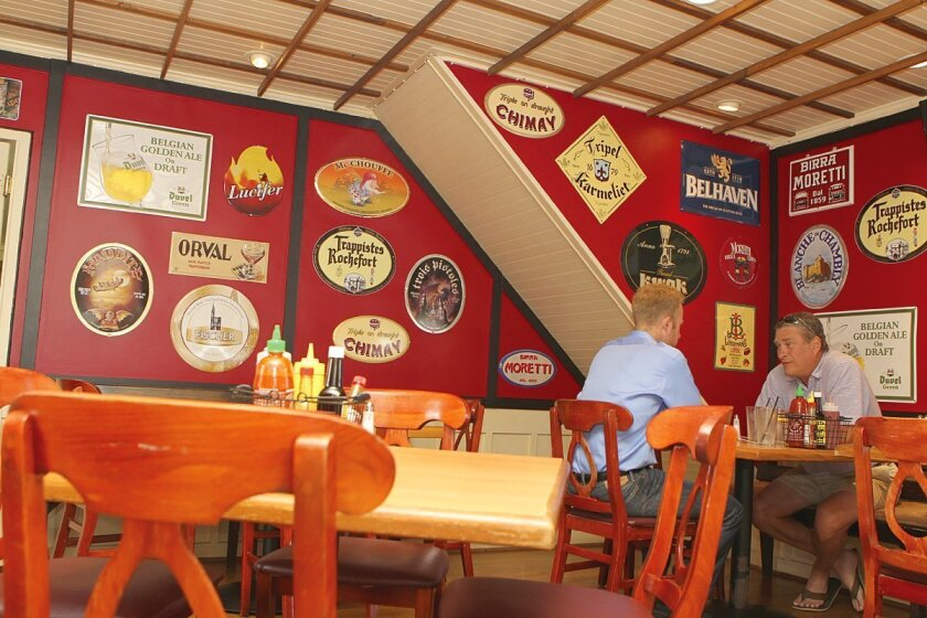 The former living room of the house occupied by The Public House in La Jolla has been remodeled into a dining room and decorated with with metal signs for some of the many brands of Belgian ales served there. Photo by Daniel K. Lew