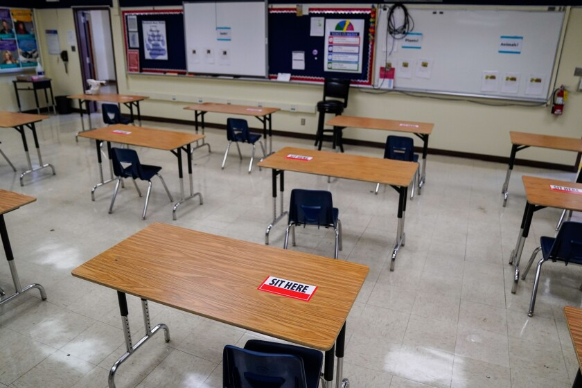 Labels on desks designate where students can sit when classrooms reopen.