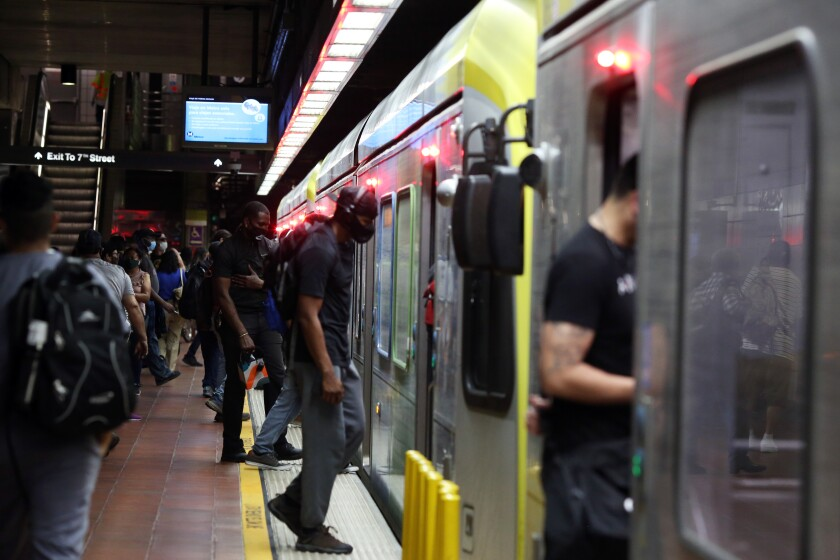 People enter a train at the 7th Street Metro Center in Los Angeles.