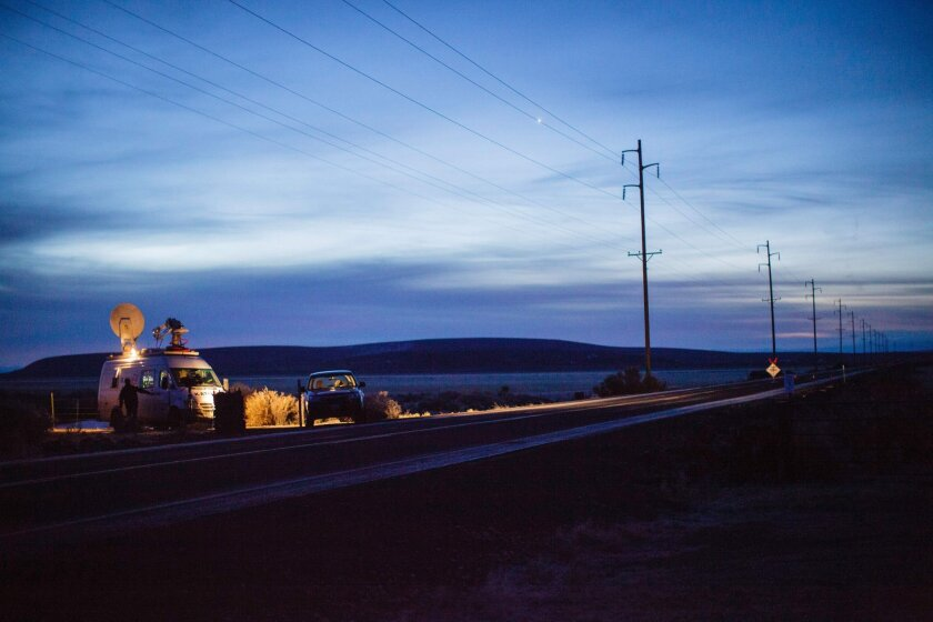 A television truck and a reporter in a car sit along Highway 78 near Malheur National Wildlife Refuge in Oregon on Jan. 27.
