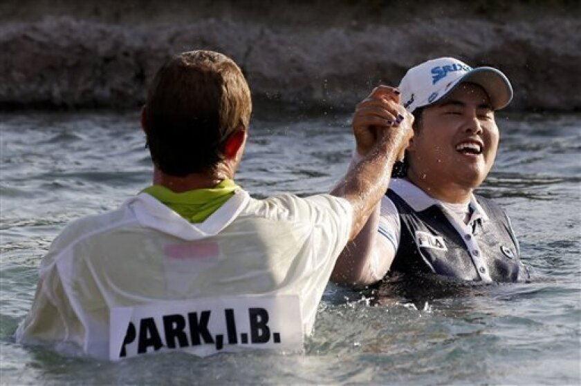 Inbee Park, right, of South Korea, celebrates after jumping into Poppy's Pond with caddie Brad Beecher after winning the LPGA Kraft Nabisco Championship golf tournament in Rancho Mirage, Calif., Sunday, April 7, 2013. (AP Photo/Chris Carlson)