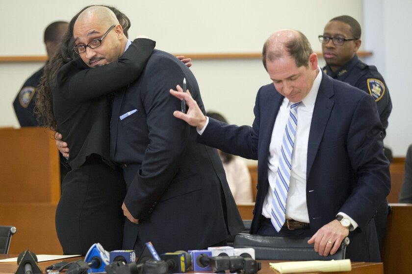 Richard Rosario, center, is hugged by his lawyers Rebecca Freedman, left, and Glenn Garber, of the Exoneration Initiative, after a judge overturns his conviction, Wednesday, March 23, 2016, in New York. The judge overturned Rosario's murder conviction and freed him while prosecutors reinvestigate his 1996 case. (AP Photo/Mary Altaffer)