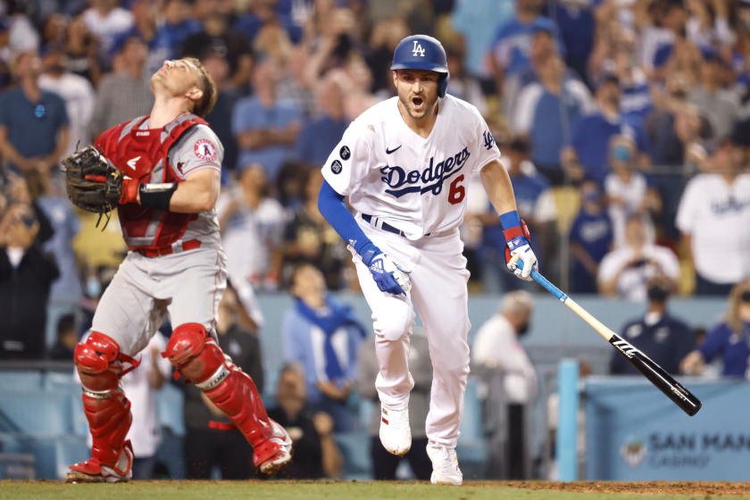 Dodgers infielder Trea Turner runs after popping up a hit while the catcher looks up.