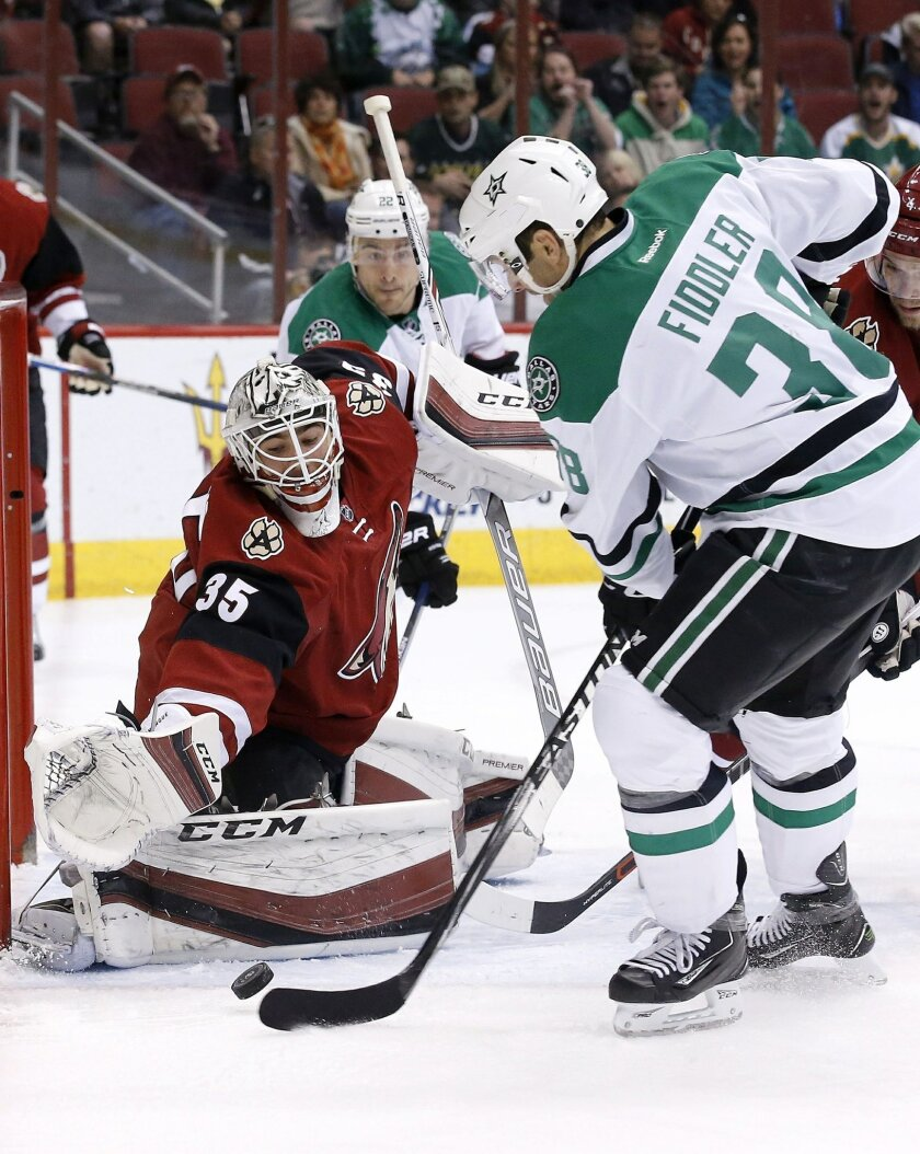 Arizona Coyotes' Louis Domingue (35) reaches over to make a save on a shot by Dallas Stars' Vernon Fiddler, right, as Stars' Colton Sceviour (22) watches during the first period of an NHL hockey game Thursday, Feb. 18, 2016, in Glendale, Ariz. (AP Photo/Ross D. Franklin)