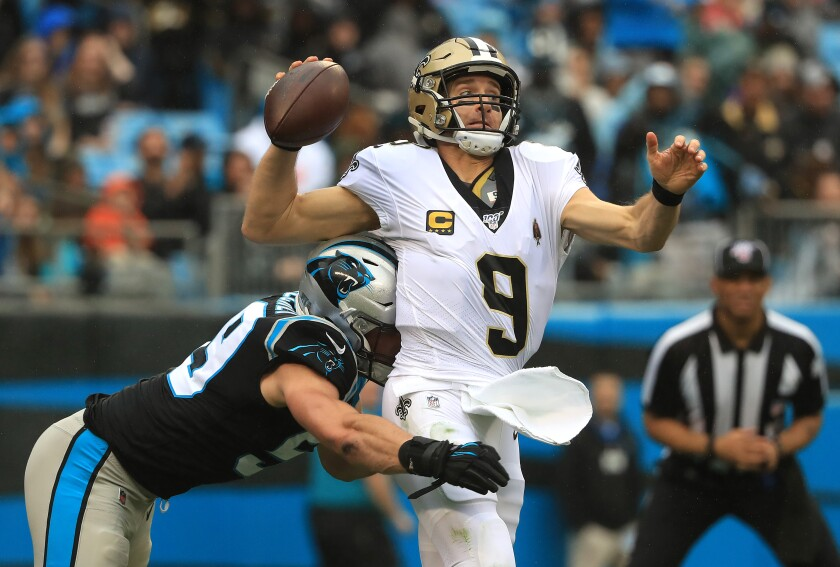 New Orleans Saints quarterback Drew Brees is hit by Carolina Panthers linebacker Luke Kuechly as he throws.