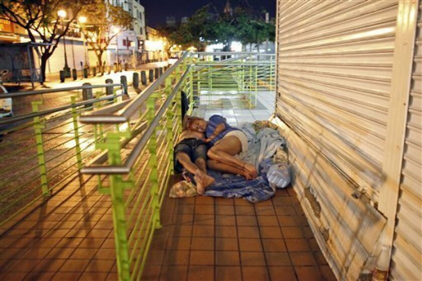 """In this June 26, 2013 photo, a homeless couple sleeps in front of a closed business in San Juan, Puerto Rico. Nearly 80 percent of previous cases involving homeless people were tied to drugs, but that financial and family problems now play a bigger part. """"We're seeing more women on the street,"""" said the Puerto Rico Pro Homeless Coalition of Coalitions' executive director. (AP Photo/Ricardo Arduengo)"""