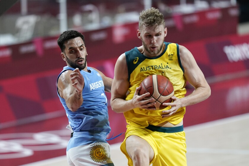 Australia's Jock Landale grabs a rebound ahead of Argentina's Facundo Campazzo, left, during a men's basketball quarterfinal round game at the 2020 Summer Olympics, Tuesday, Aug. 3, 2021, in Saitama, Japan. (AP Photo/Charlie Neibergall)