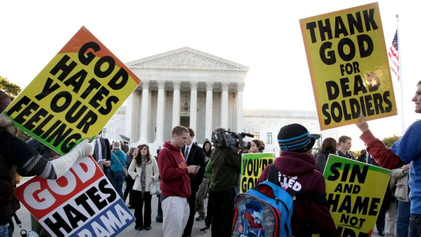Members of the Westboro Baptist Church picket in front of the Supreme Court in Washington, Wednesday