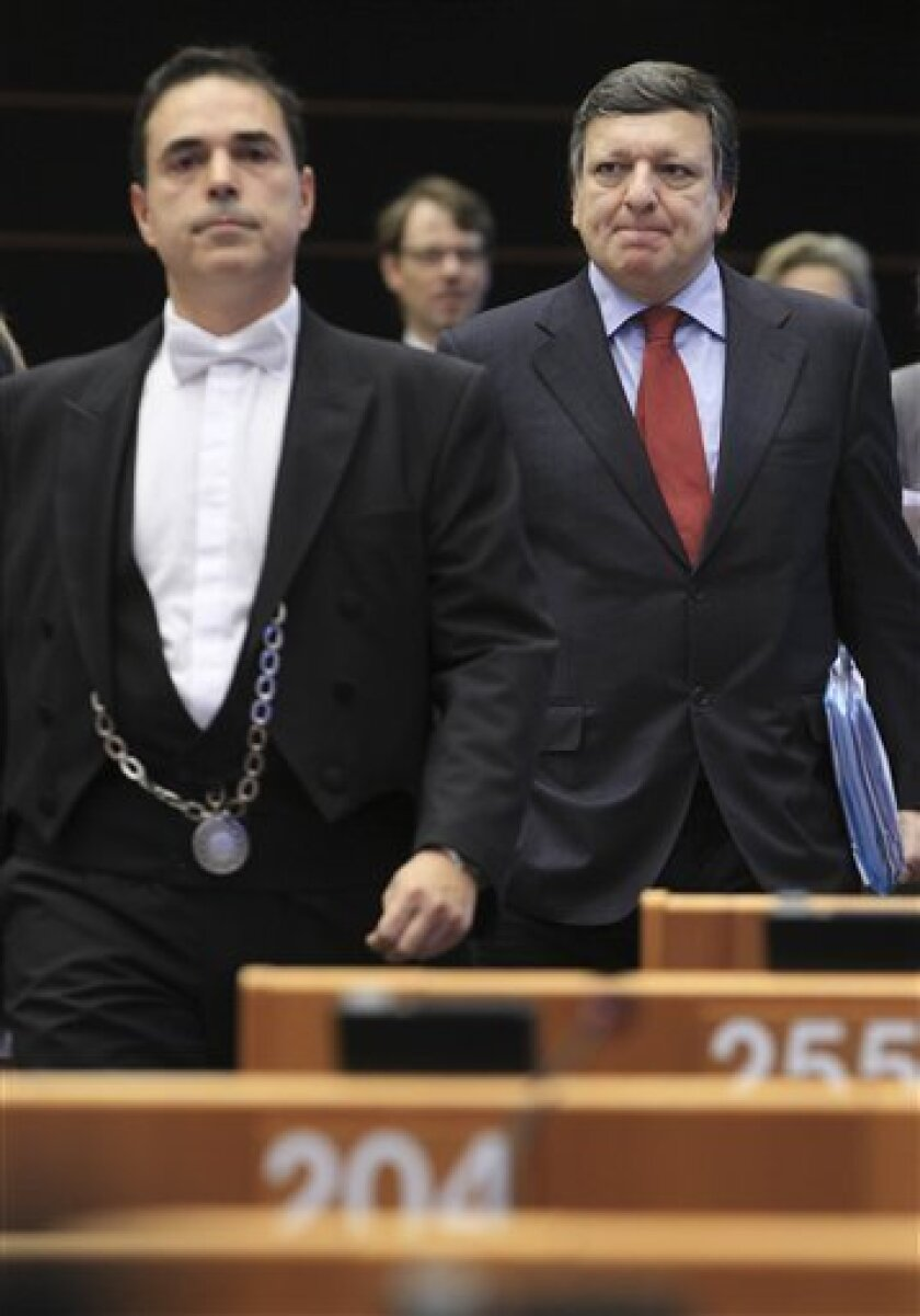 European Commission President Jose Manuel Barroso, right, arrives at the Hemicycle of the European Parliament in Brussels, Wednesday, Oct. 12, 2011. The European Union hopes to push its member states to take firmer action on the debt crisis when it presents Wednesday a broad new plan to fight market turmoil, from strengthening weak banks to lowering Greece's debt burden. The plan is the boldest attempt yet to stem the crisis, which has linked the fortunes of highly indebted states like Greece, Ireland and Portugal with those of the banks that own those countries' bonds. (AP Photo/Yves Logghe)