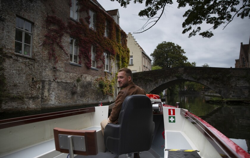 Fourth generation tour boat operator Michiel Michielsens drives his electric boat down a canal in Bruges, Belgium, Wednesday, Sept. 2, 2020. Europe's leanest summer tourist season in history is starting to draw to a close, six months after the coronavirus hit the continent. COVID-19 might tighten its grip over the coming months, with losses piling up in the tens of billions of euros across the 27-nation European Union. In the Belgian city of Bruges, white swans instead of tourist boats rule the canals, hotels stand empty and museums count their losses. (AP Photo/Virginia Mayo)