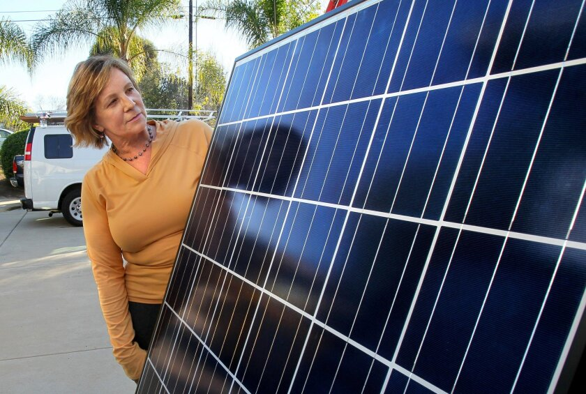 Homeowner Diane Shutt gets a close look at one of the many solar panels that'll soon be installed on the roof of her Vista home by workers from Sullivan Solar Power, of San Diego.