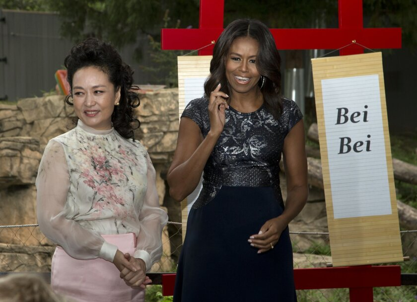 """First lady Michelle Obama and China's first lady Peng Liyuan, reveal the name of the panda born at the Smithsonian's National Zoo in Washington on Aug. 22 to Mei Xiang, during a visit to the zoo in Washington, Friday, Sept. 25, 2015. The name is Bei Bei, which means """"precious treasure."""" It was chosen by both the Chinese and American first ladies. (AP Photo/Manuel Balce Ceneta)"""