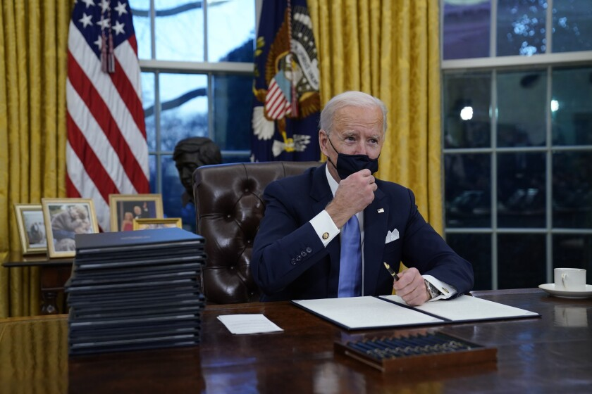 President Biden adjusts his face mask as he signs his first executive orders in the White House on Jan. 20.