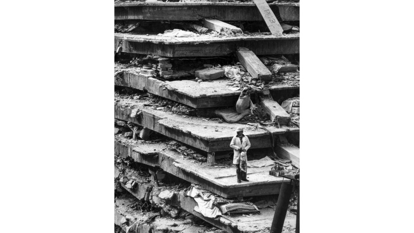 Sept. 19, 1985: A man stands on the wreckage of the General Hospital in Mexico City where collapsing floors killed 277 in earthquake.