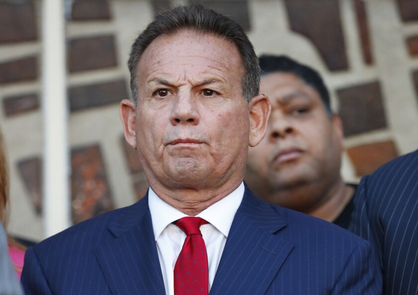 FILE - In this Jan. 11, 2019 file photo, suspended Broward County Sheriff Scott Israel listens to comments by his attorney at a news conference after new Florida Gov. Ron DeSantis suspended Israel in Fort Lauderdale, Fla., over his handling of February's massacre at Marjory Stoneman Douglas High School. Florida Senate special master Dudley Goodlette is recommending that the sheriff suspended over his handling of shootings at a Parkland high school and the Fort Lauderdale airport should be reinstated. (AP Photo/Wilfredo Lee, File)