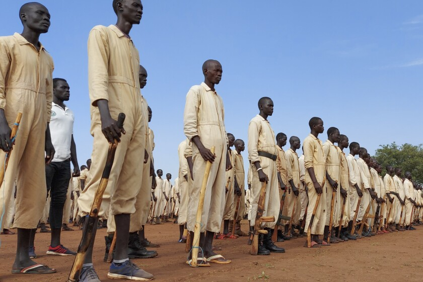 FILE - In this Saturday, June 27, 2020 file photo, trainees parade with the wooden mock guns which they use to train with, during the visit of the defense minister to a military training center in Owiny Ki-Bul, Eastern Equatoria, South Sudan. (AP Photo/Maura Ajak, File)