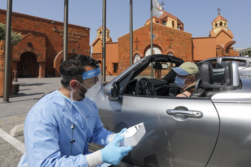 Edward Zaghikian gives Simone McFarland the result of her antibody test at a drive-through testing center May 9 in Burbank.