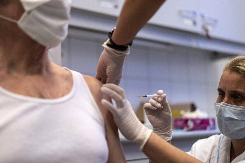A man receives a shot of Russian vaccine Sputnik V at Central Hospital of the Hungarian Defence Forces (military) in Budapest, Hungary, Friday, Feb. 12, 2021, as the vaccination with Sputnik V against the new coronavirus begins in the country. (Zsolt Szigetvary/MTI via AP)