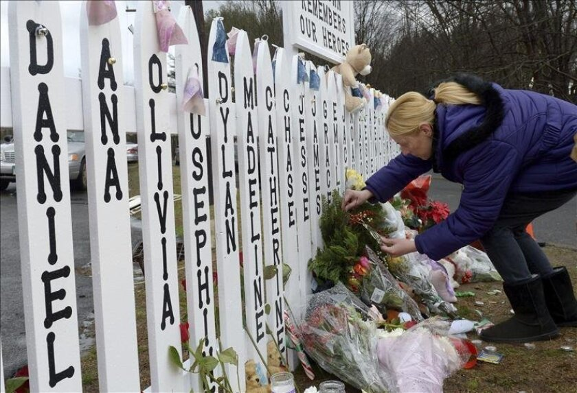 A woman places flowers on a fence on which are inscribed the names of the victims killed in Sandy Hook Elementary School in Newtown, Conn.