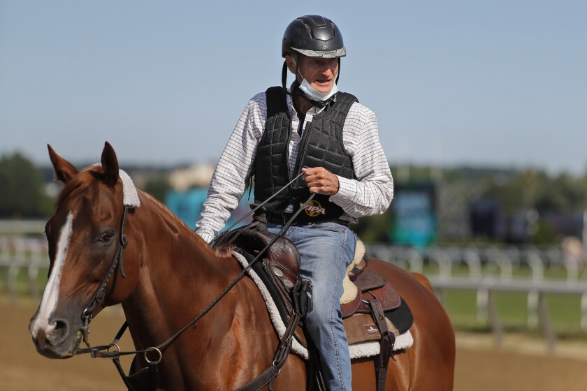 Tiz The Law trainer Barclay Tagg rides another horse on the main track during workouts at Belmont Park on Wednesday.